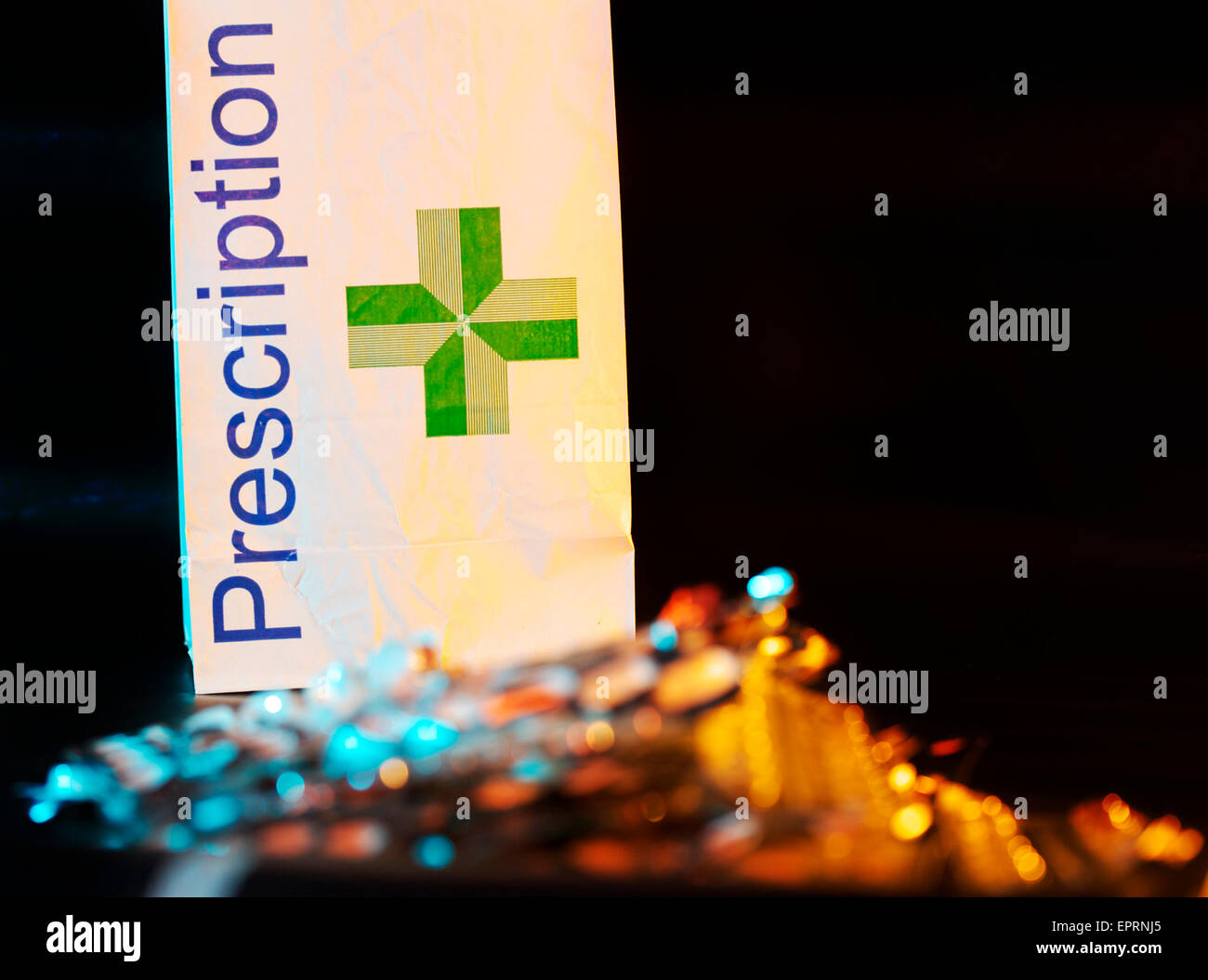 NHS pharmacy prescription paper bag with foil tablet packets/blister packs in the foreground - Stock Image