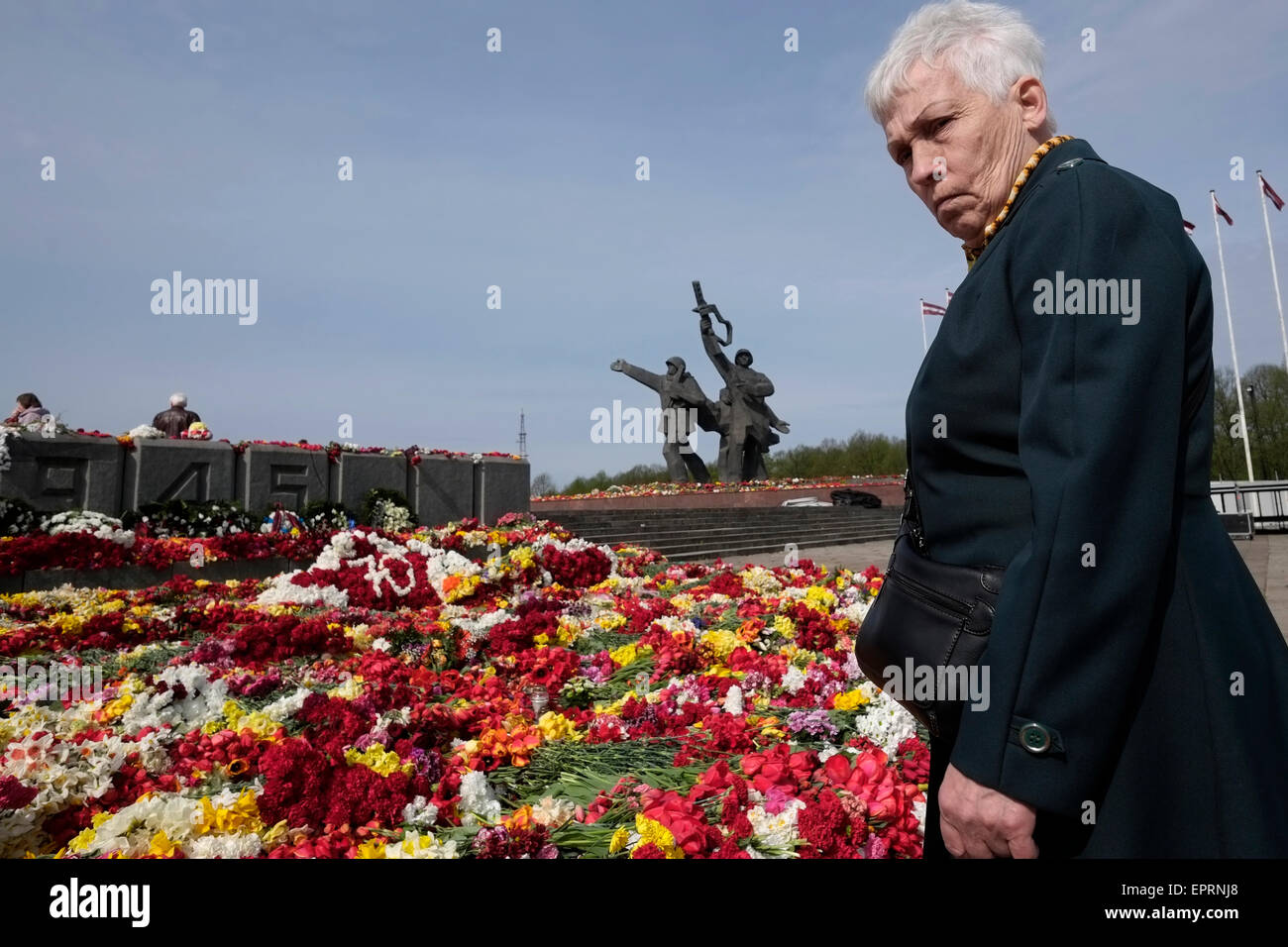Elderly woman gazing at wreaths marking 70 years since victory over Nazi Germany at the Soviet victory monument - Stock Image