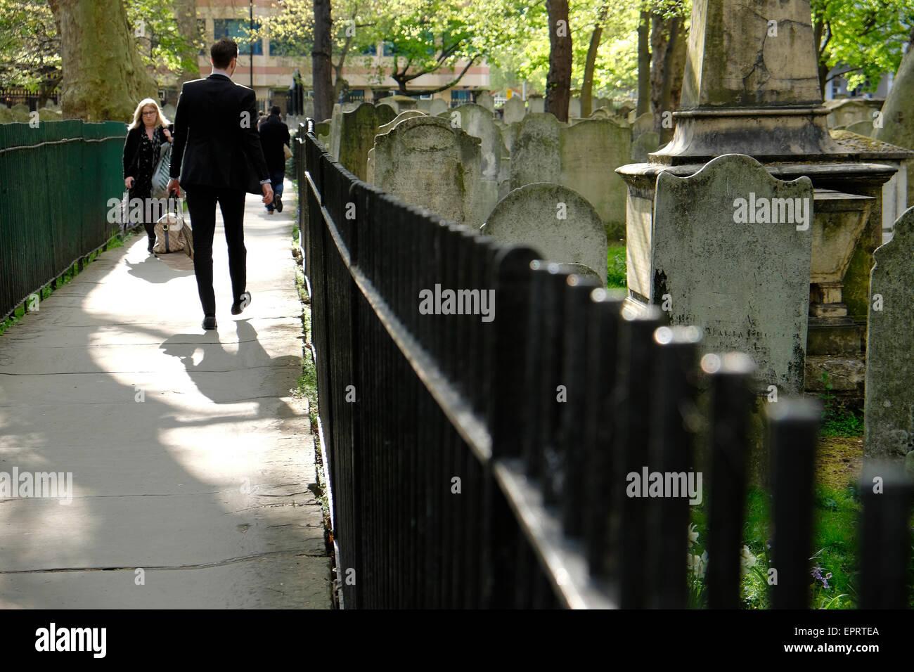 People walking along the  graveyard path or walkway in Bunhill Fields Cemetery, Islington, City of London EC1  UK - Stock Image