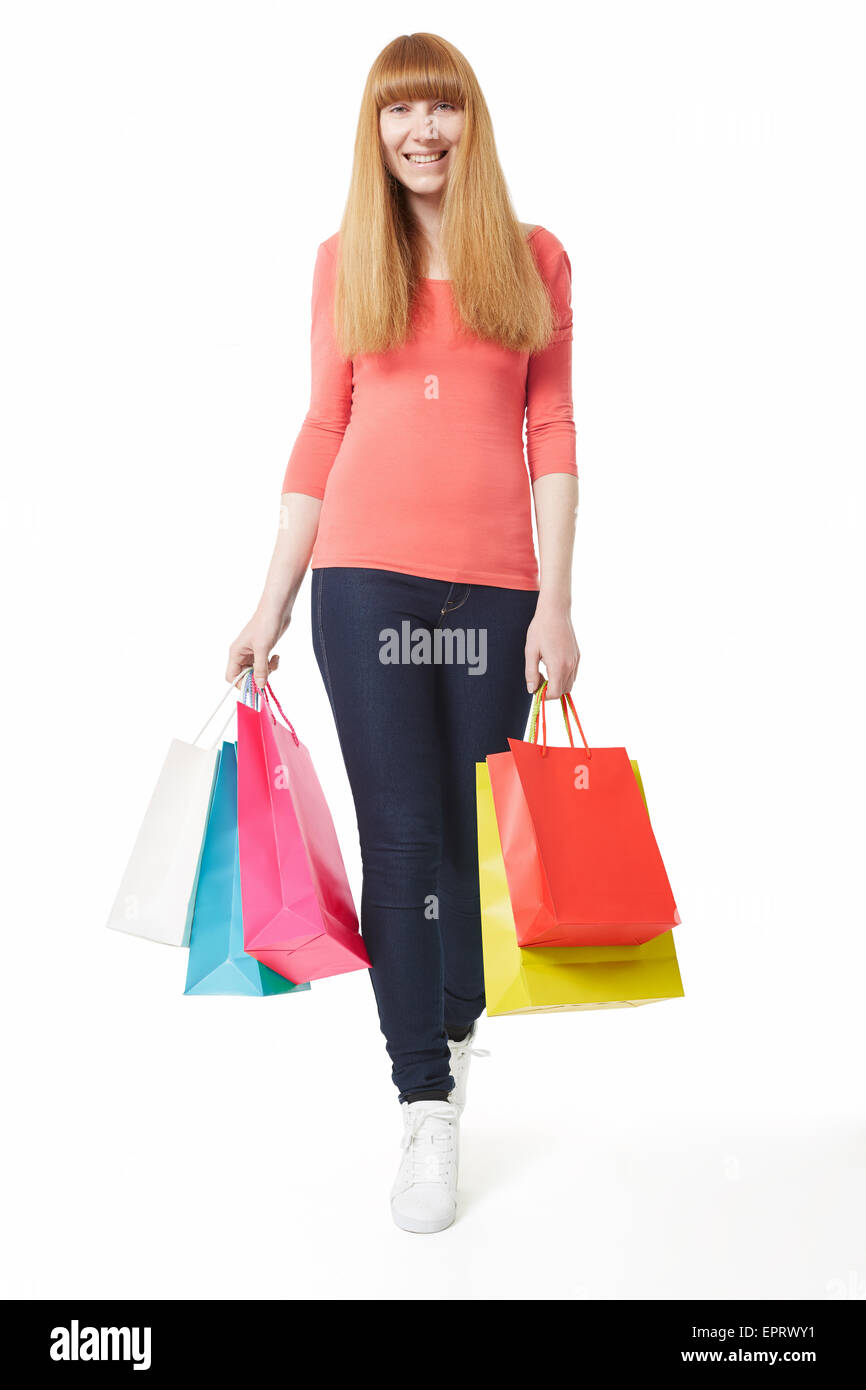 Young, smiling woman walking with shopping bags - Stock Image