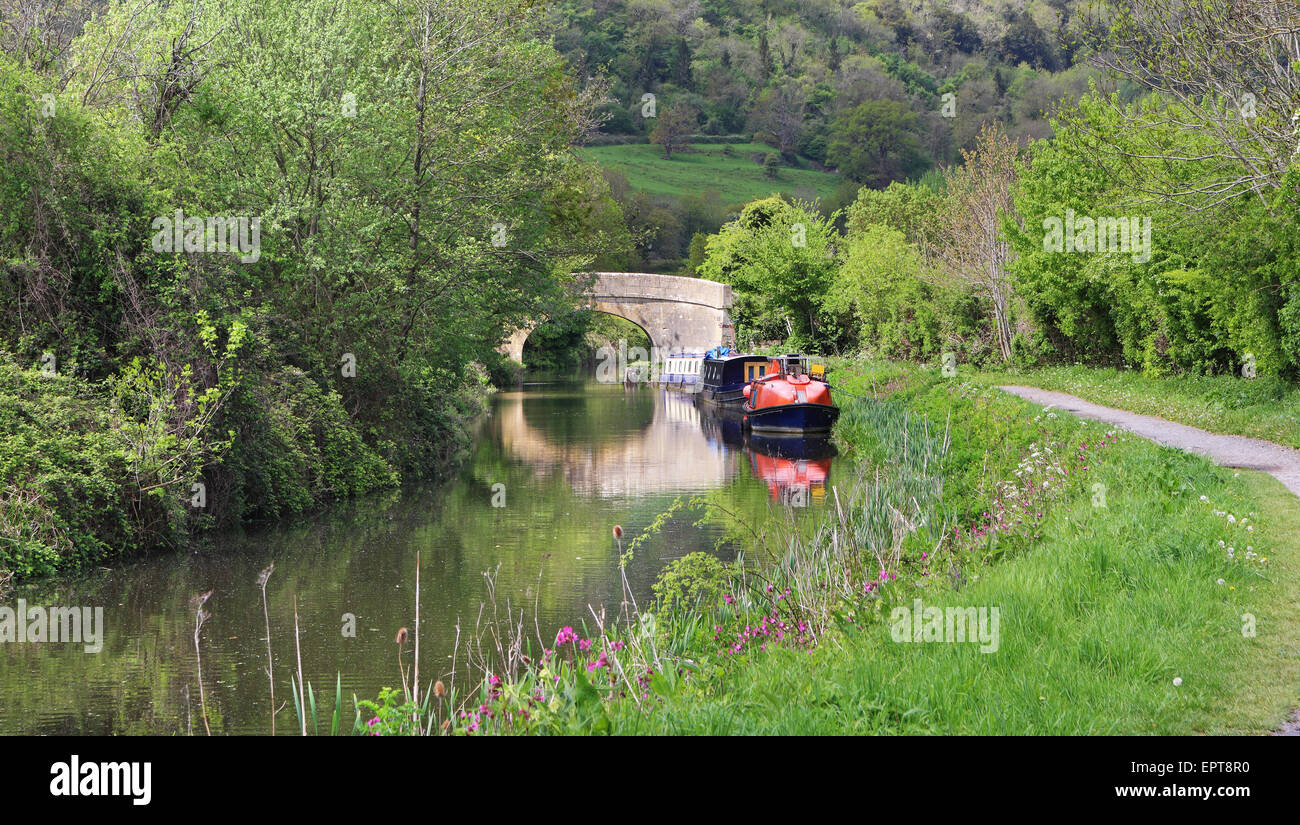 Narrowboats on the Kennet & Avon Canal in Wiltshire with stone bridge Stock Photo