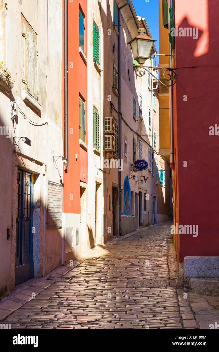 Sunlit street in Rovinj, Croatia with venetian styled houses, ornate street lamp and shinney cobble stones - Stock Image