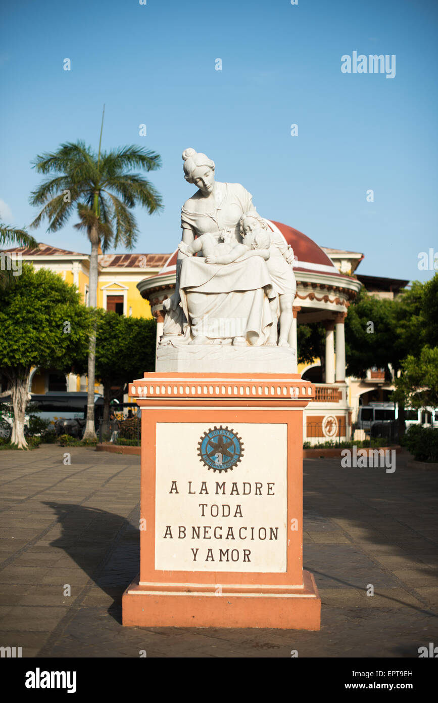 A statue devoted to motherhood in Parque Central. The inscription reads 'Mother of all devotion and love.' - Stock Image