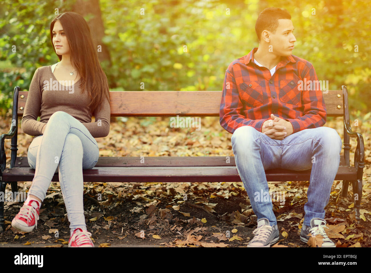 Young couple in quarrel sitting on bench in park - Stock Image