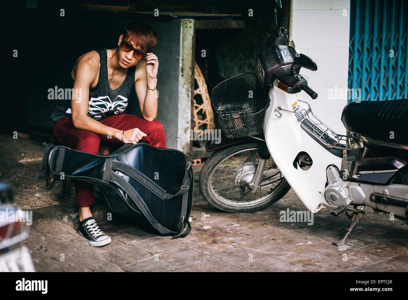 35ccb664bf asian fashion street teenager in style sunglasses with guitar case and  motorbike