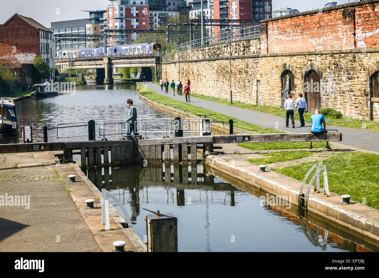 Man Sitting on Lock Gates Leeds and Liverpool Canal,Leeds,West Yorkshire Stock Photo