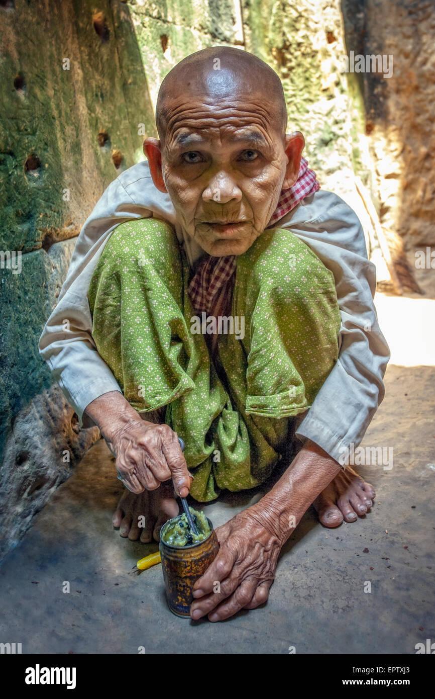 Close up of monk in Angkor Wat preparing offering - Stock Image