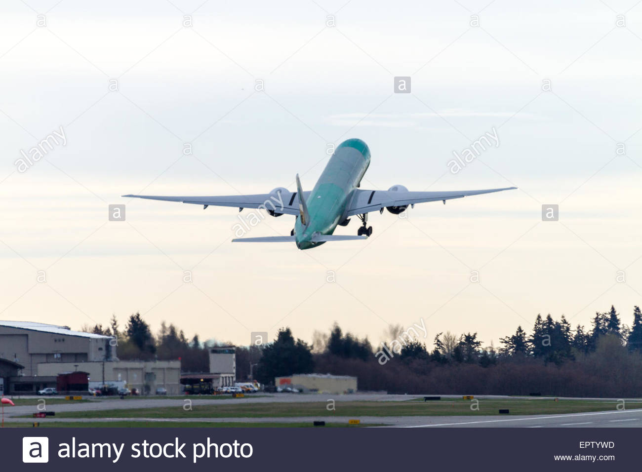 An unpainted Boeing 777 takes off from Paine Field in Everett - Washington on test flights - Stock Image