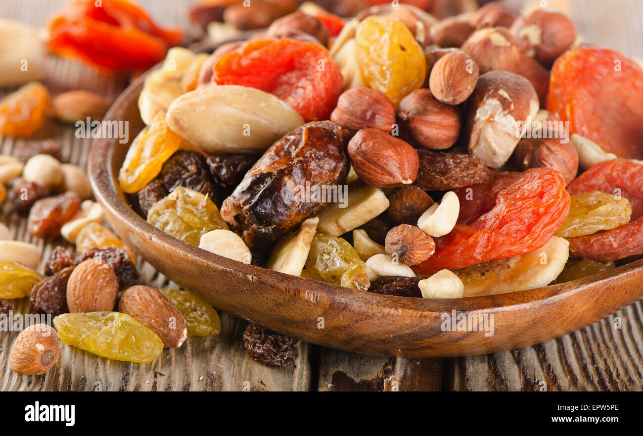 Healthy Nuts and dried  fruits on a wooden background. - Stock Image