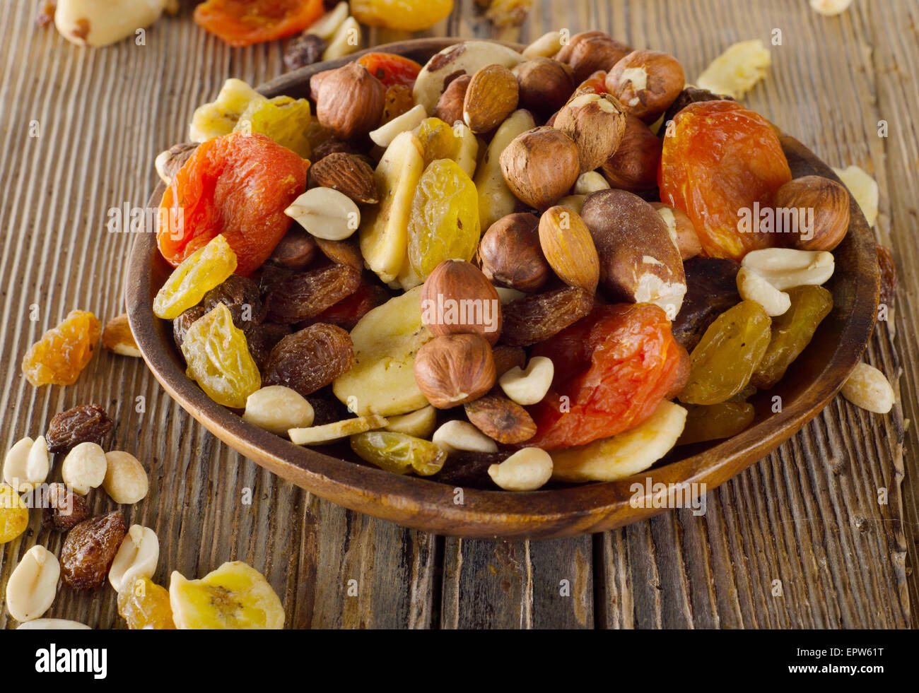 Nuts and dried  fruits on a wooden background. - Stock Image