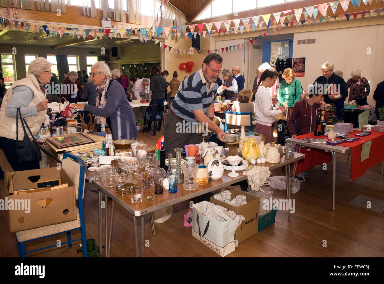 Stalls selling all kinds of wares at a Christian Aid Week coffee morning to raise funds for the charity, Liphook, - Stock Image