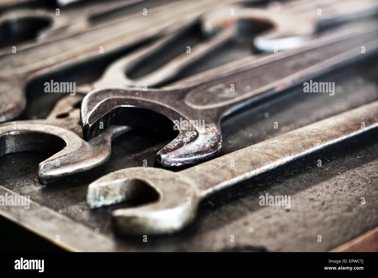 Collection of used dirty old grunge metal wrenches and spanners lying on a workbench in an engineering workshop - Stock Image