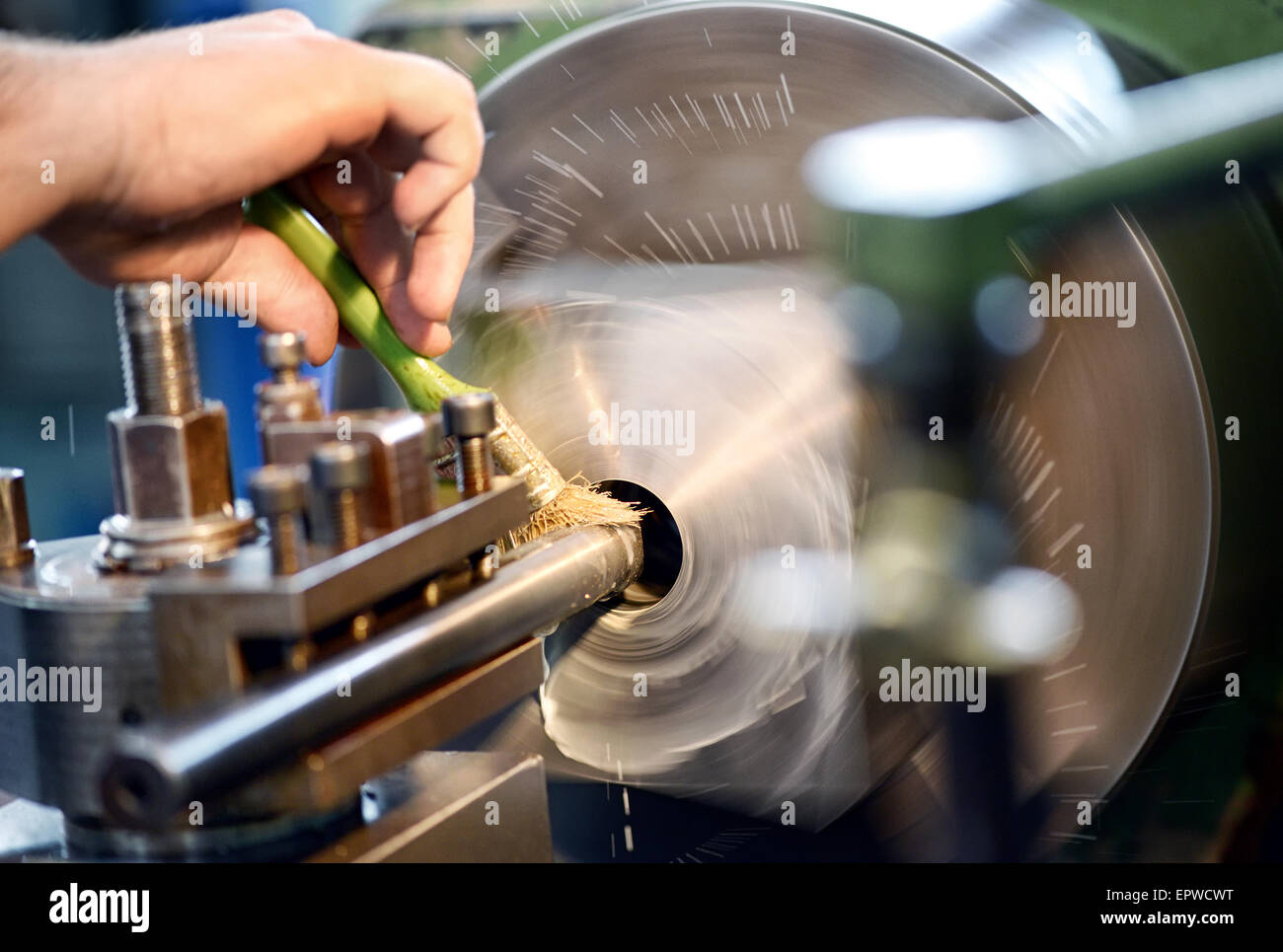 Man placing lubricating oil on a lathe in an engineering or industrial workshop - Stock Image