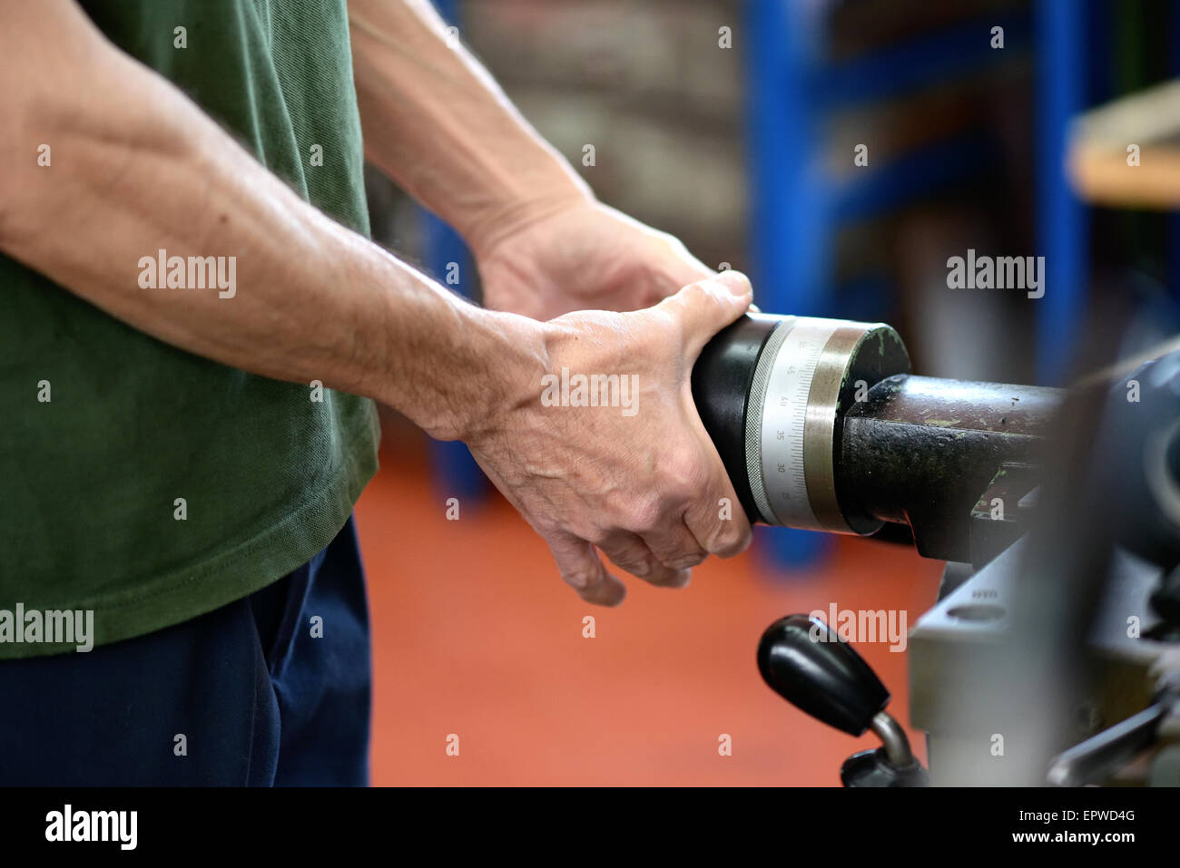Close up of the hands of a man working on machinery in an engineering workshop or factory - Stock Image