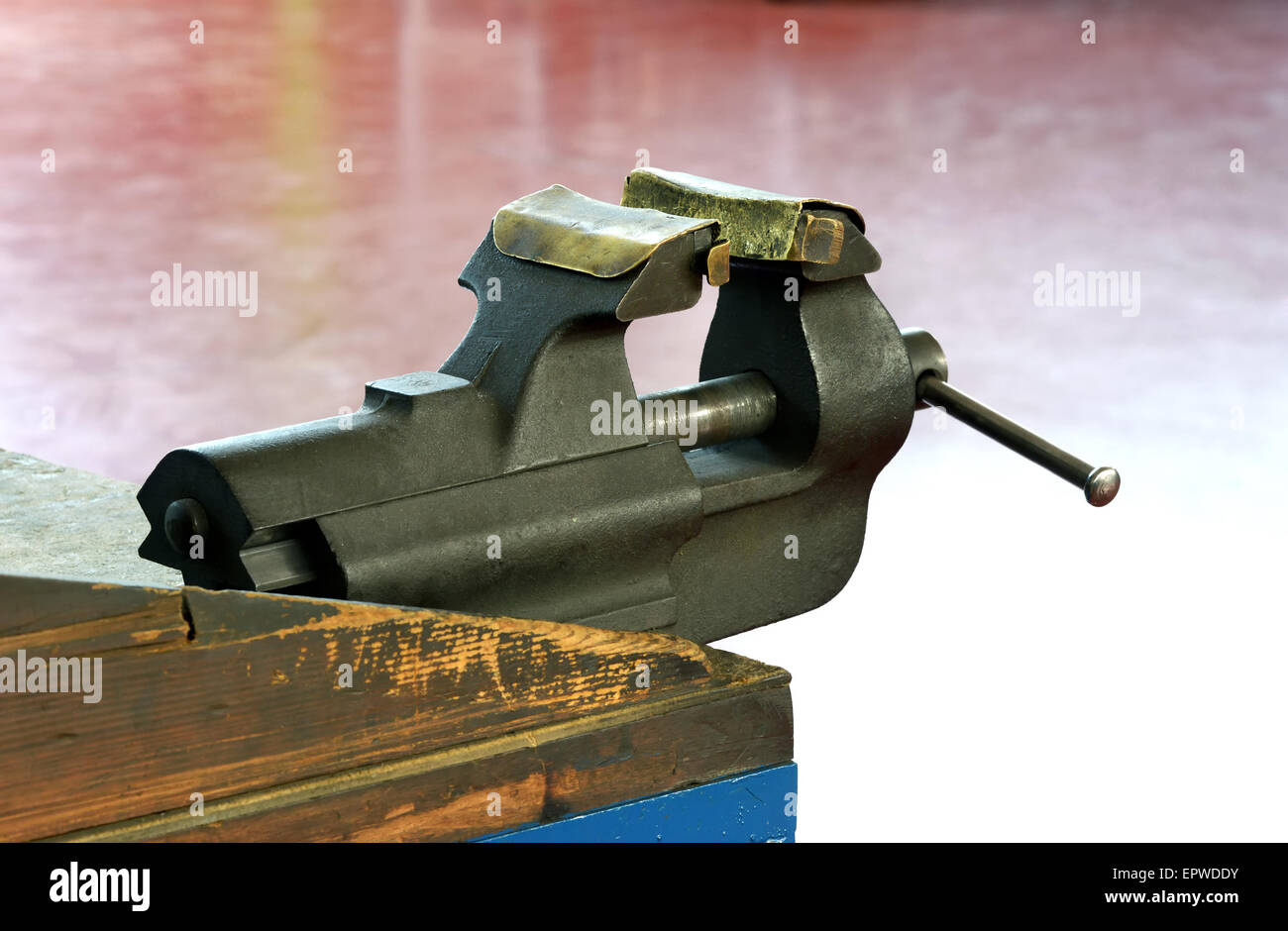 Steel vice mounted on a wooden workbench with metal jaws - Stock Image