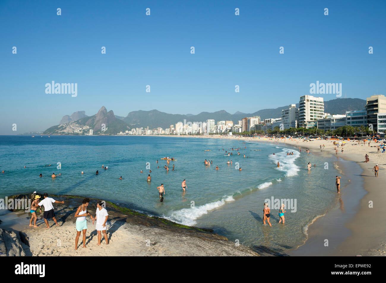 RIO DE JANEIRO, BRAZIL - JANUARY 17, 2015: Beachgoers relax on on the rocks at the Arpoador end of Ipanema Beach. - Stock Image