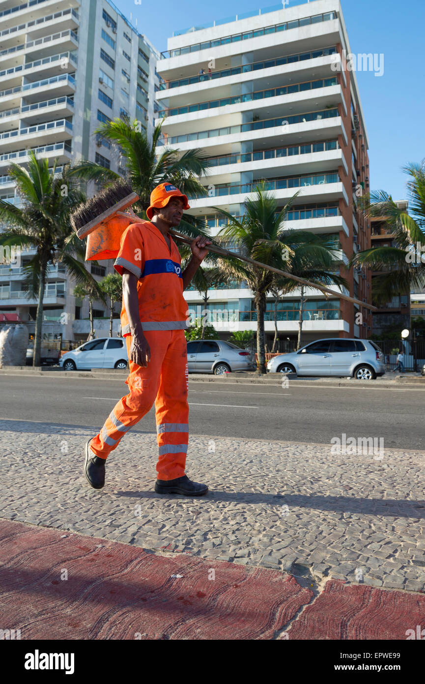RIO DE JANEIRO, BRAZIL - FEBRUARY 20, 2015: Member of COMLURB municipal cleaning service walks with broom in trademark - Stock Image