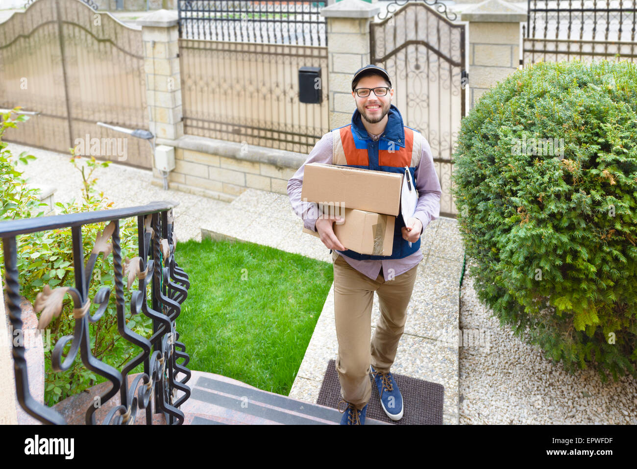 Courier Delivering a Package up on the stairs - Stock Image