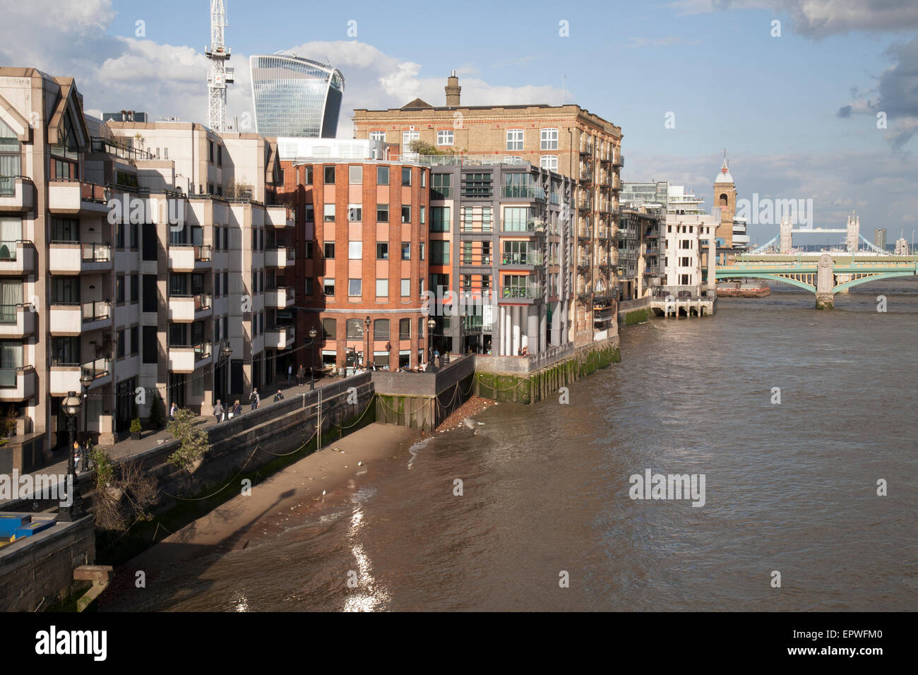 A view of riverside buildings on the banks of the River Thames in London, England. - Stock Image