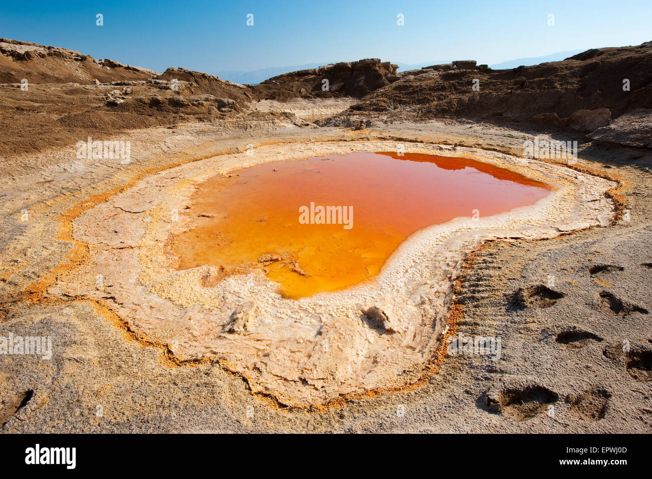 Sinkhole or open pit with orange salty water on the shore's of the dead sea at the end of the summer when the water Stock Photo