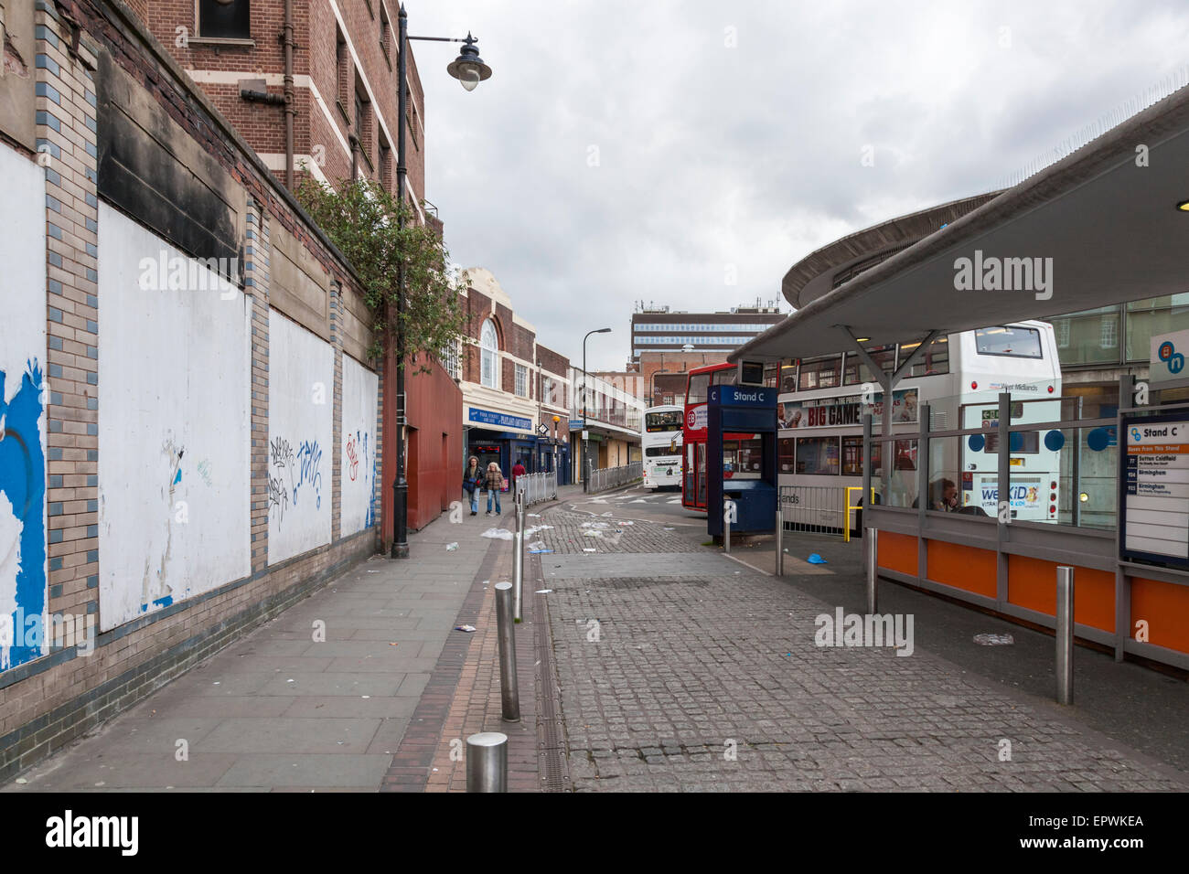 Run down area in Walsall town centre with closed down and boarded up shops  and litter