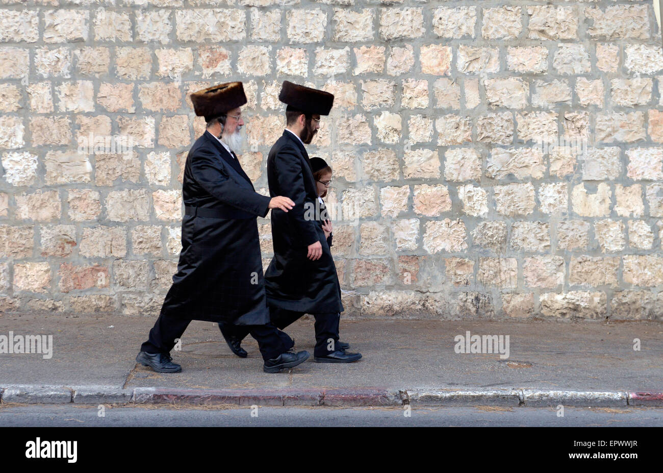 Two Jewish men and a child walking on the street a few days before sukkot or the 'feast of tabernacles - Stock Image