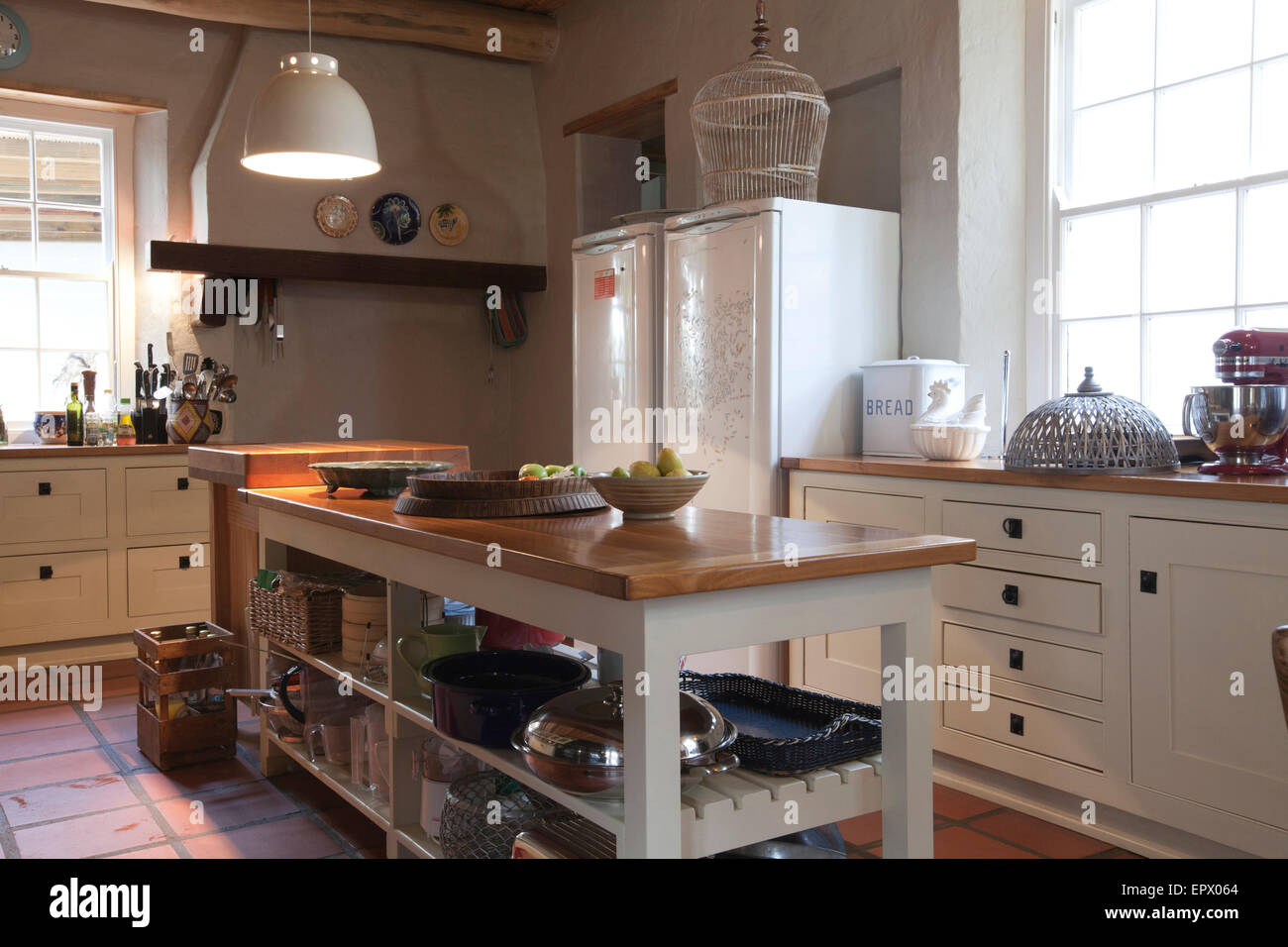 farm style kitchen with wooden island displaying various pots in
