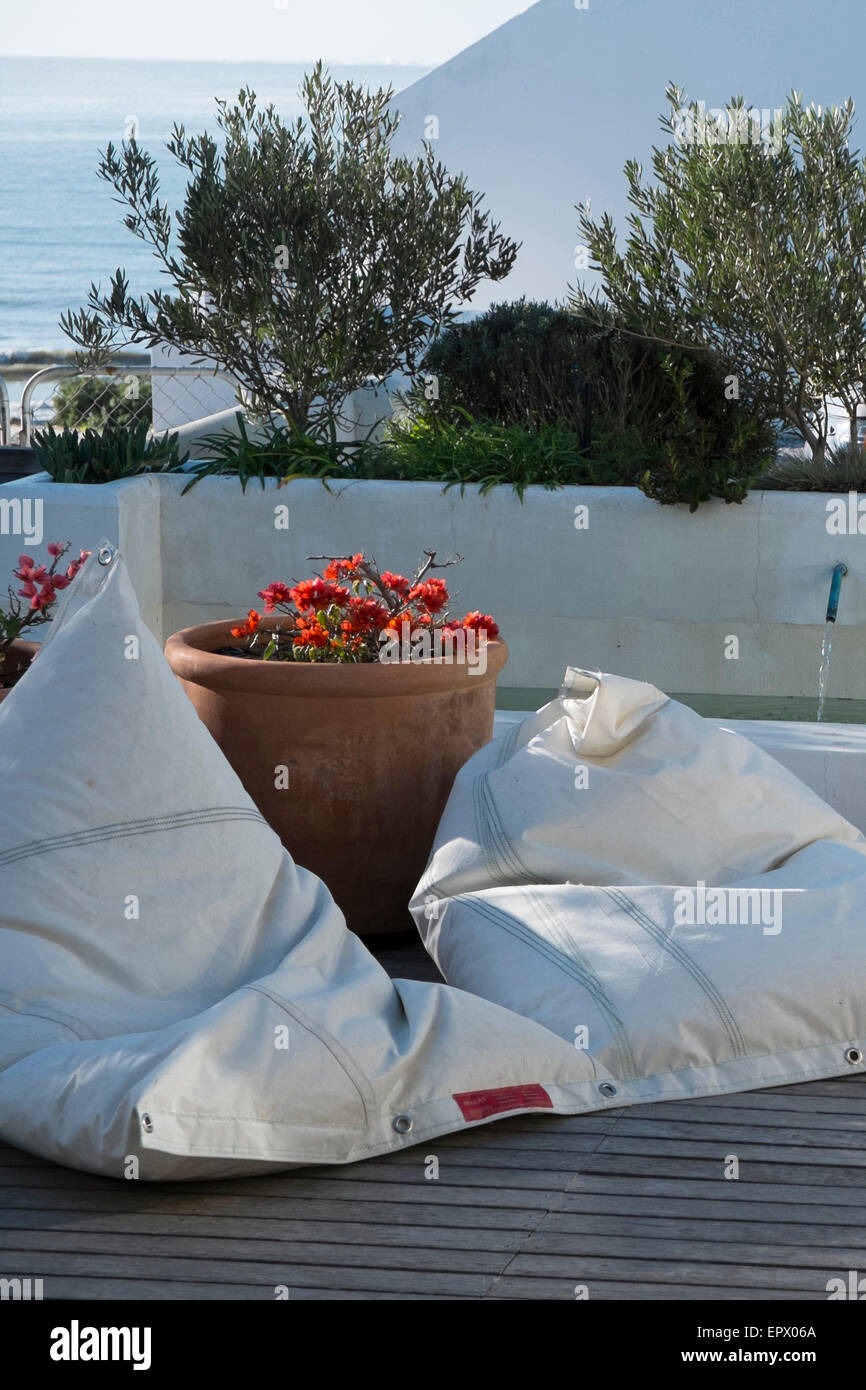 Sailcloth bean bags on wooden deck next to swimming pool and potted orange bougainvillea, South Africa - Stock Image