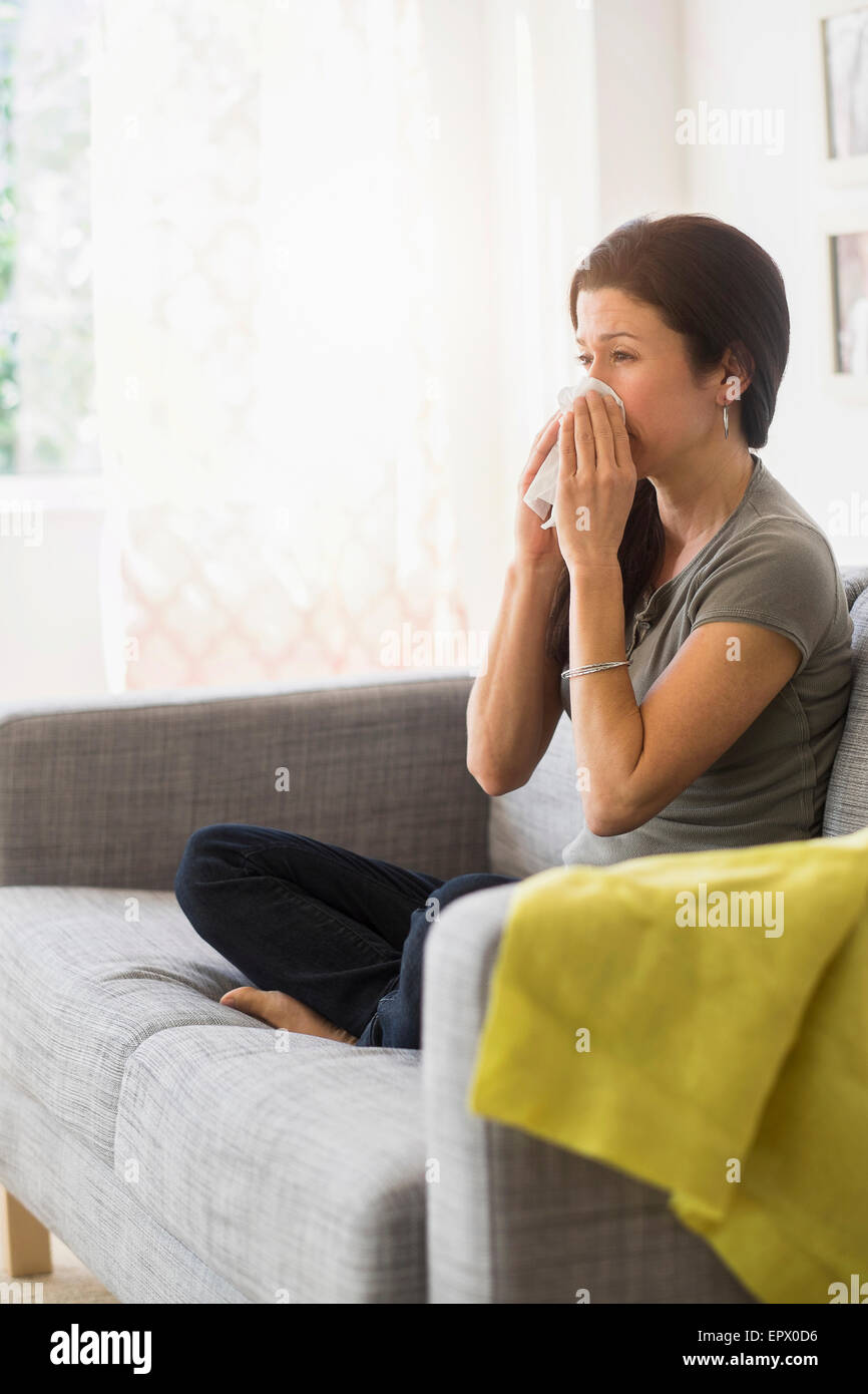 Woman blowing her nose on sofa - Stock Image