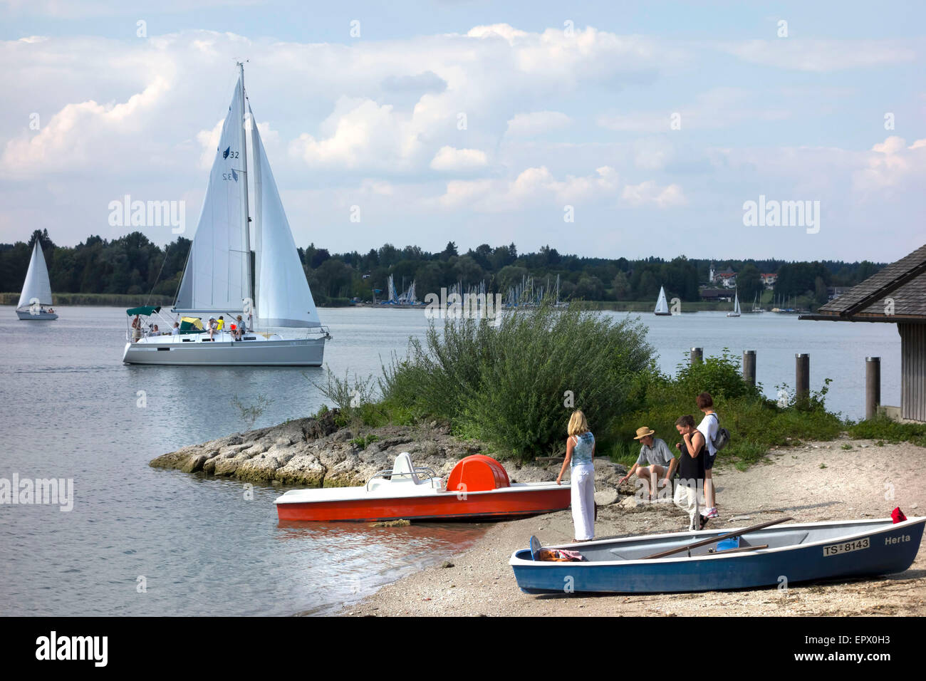 People on beach with sail boat passing bye, Herreninsel Chiemsee Upper Bavaria Germany - Stock Image
