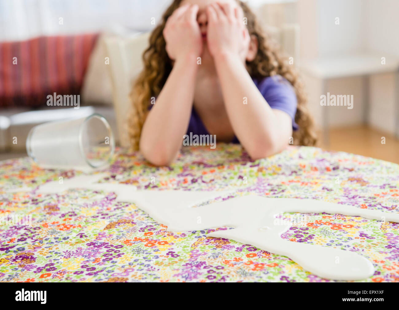 Sad girl (10-11) spilled out milk - Stock Image