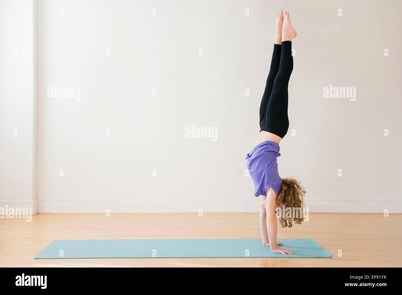 Girl (10-11) doing handstand - Stock Image