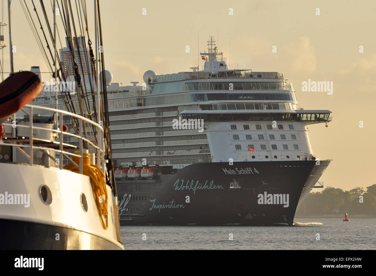 Cruiseship 'Mein Schiff 4' passing a traditional sailing ship in the early morning sun. - Stock Image