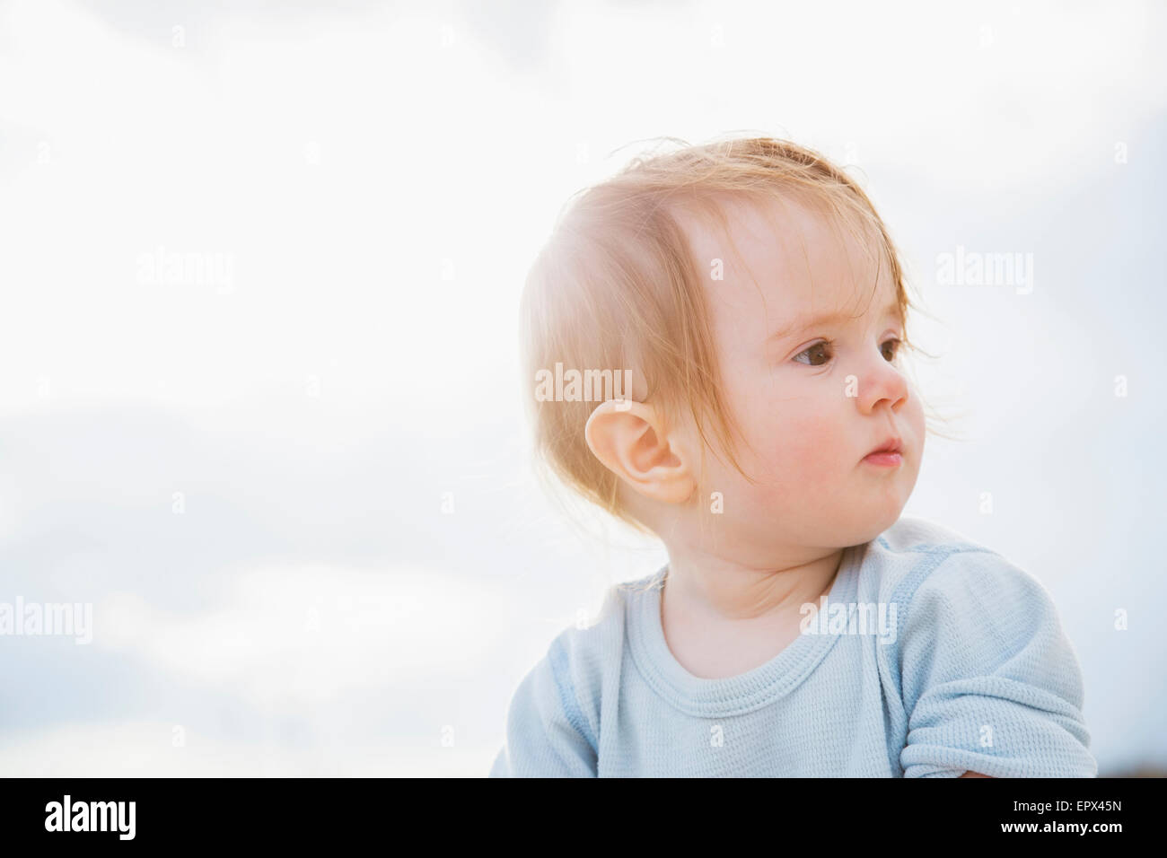Baby girl (6-11 months) looking away - Stock Image