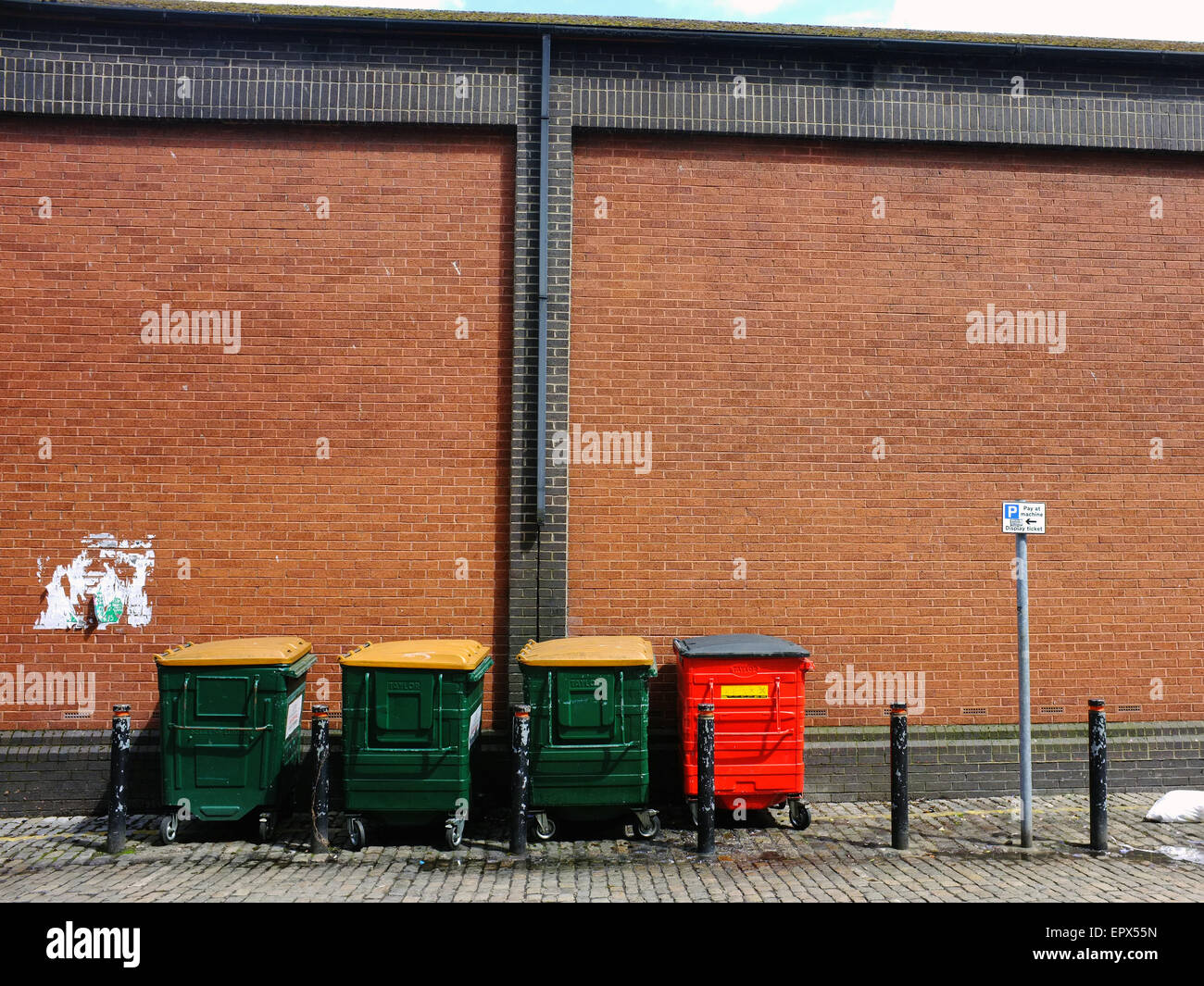 A row of green and red rubbish bins along a street in Bristol. - Stock Image