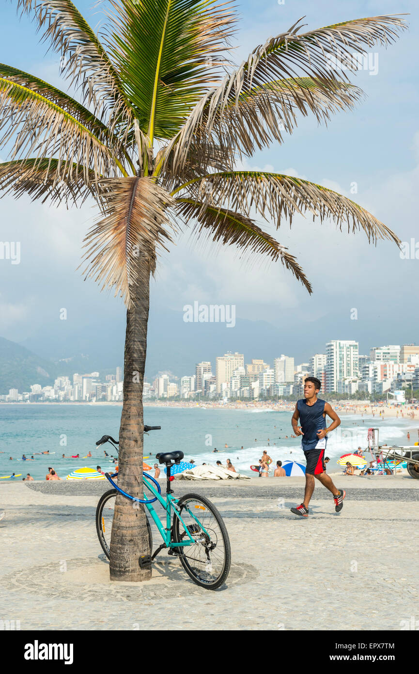 RIO DE JANEIRO, BRAZIL - MARCH 22, 2015: Jogger passes a bicycle locked to a palm tree on the boardwalk at Arpoador near Ipanema Stock Photo