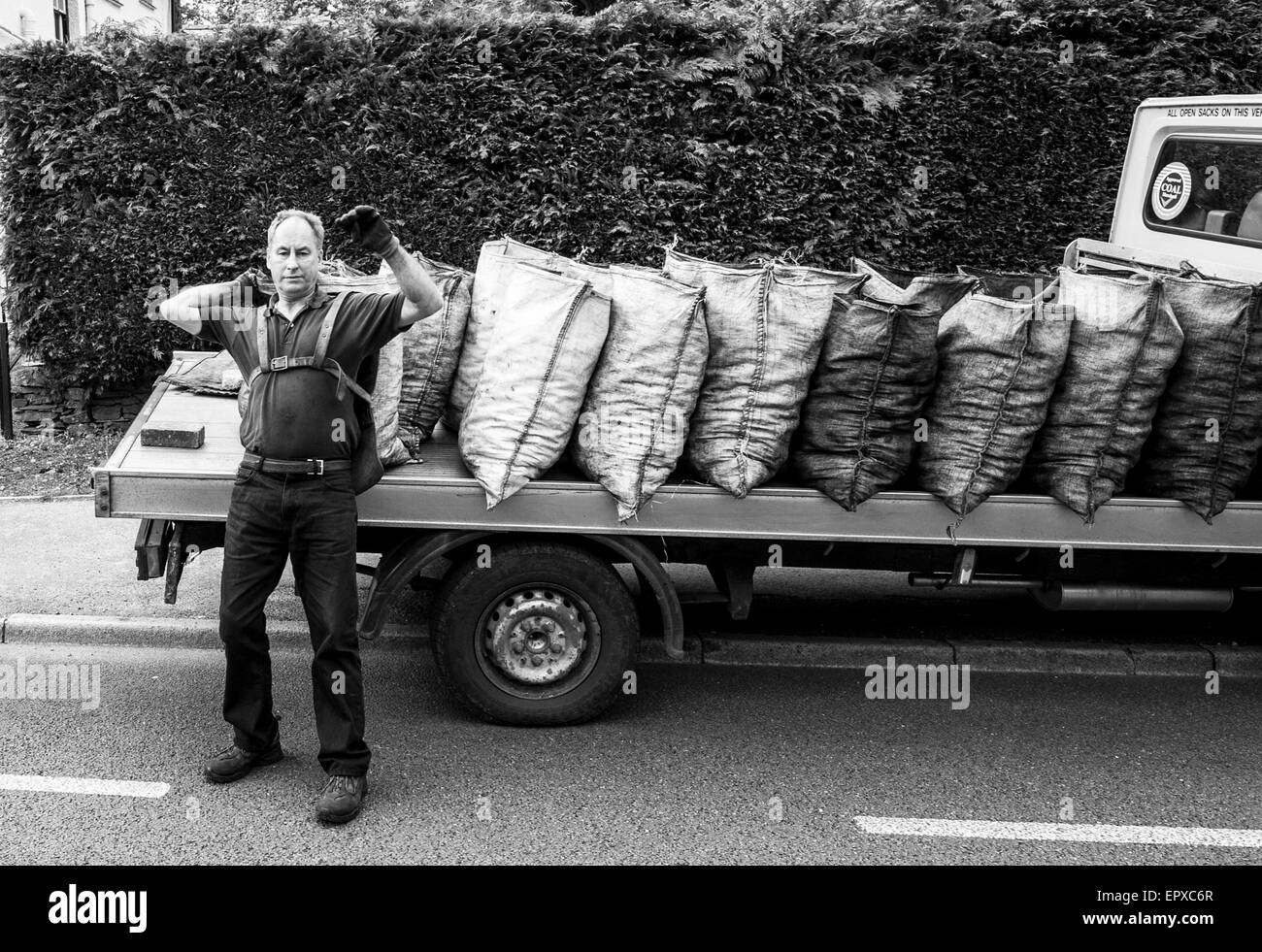 traditional coal man delivery open sacks coal from lorry - Stock Image