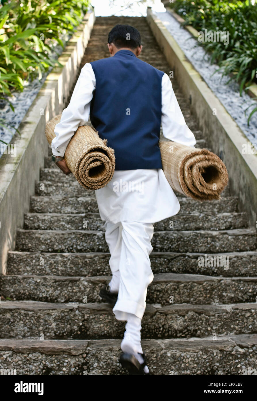 A man carries yoga mats up a staircase to the  open-air pavilion at Ananda in the Himalayas, The Palace Estate, - Stock Image