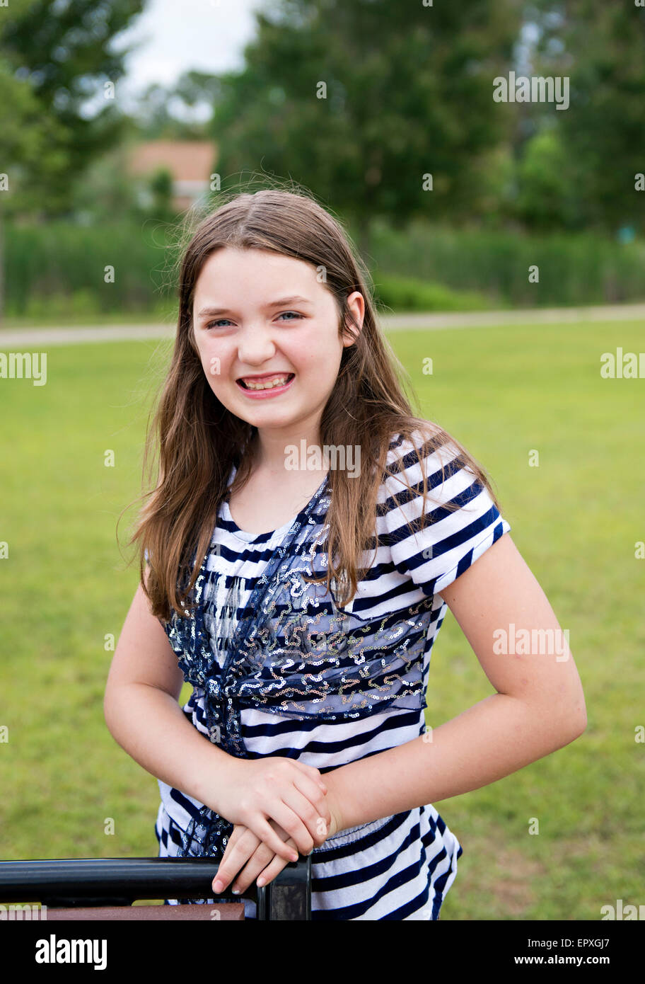 Teenage girl posing for a portrait at an outdoor park - Stock Image