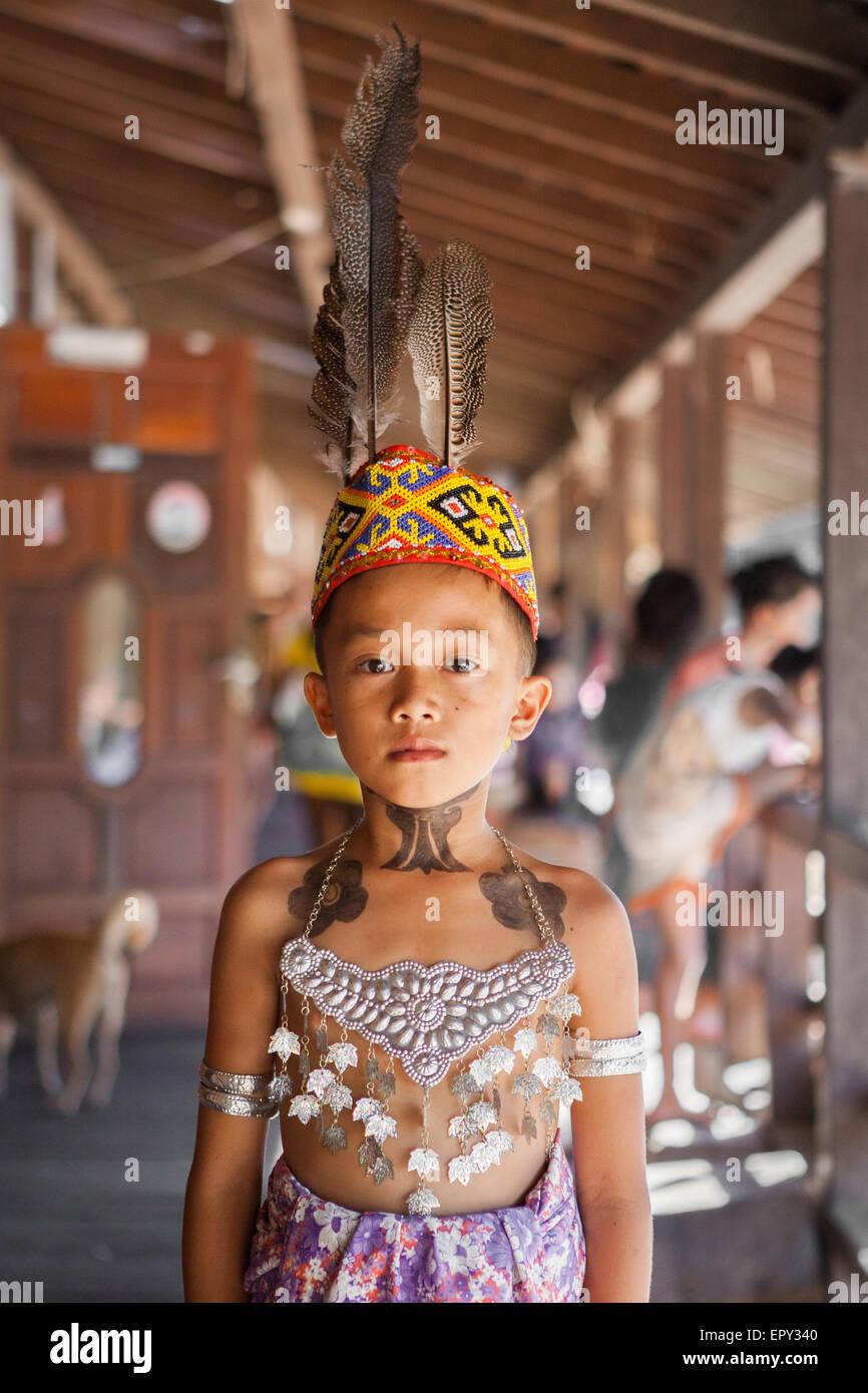 Portrait of Dayak Iban boy at Sungai Utik communal longhouse in West Kalimantan, wearing head accessories made of - Stock Image