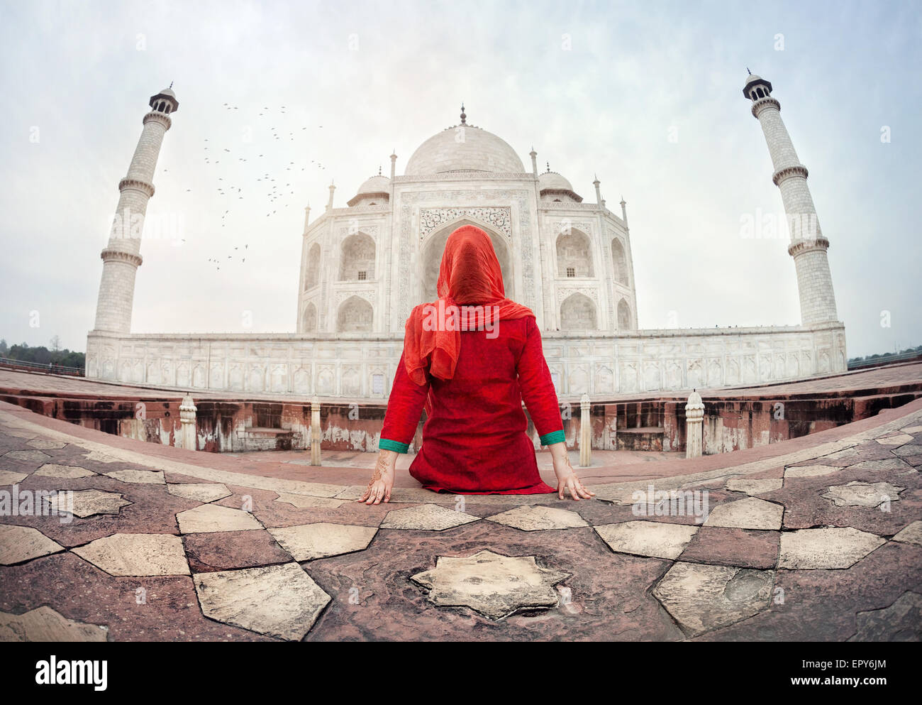 Woman in red costume sitting on the floor and looking at Taj Mahal in Agra, Uttar Pradesh, India - Stock Image