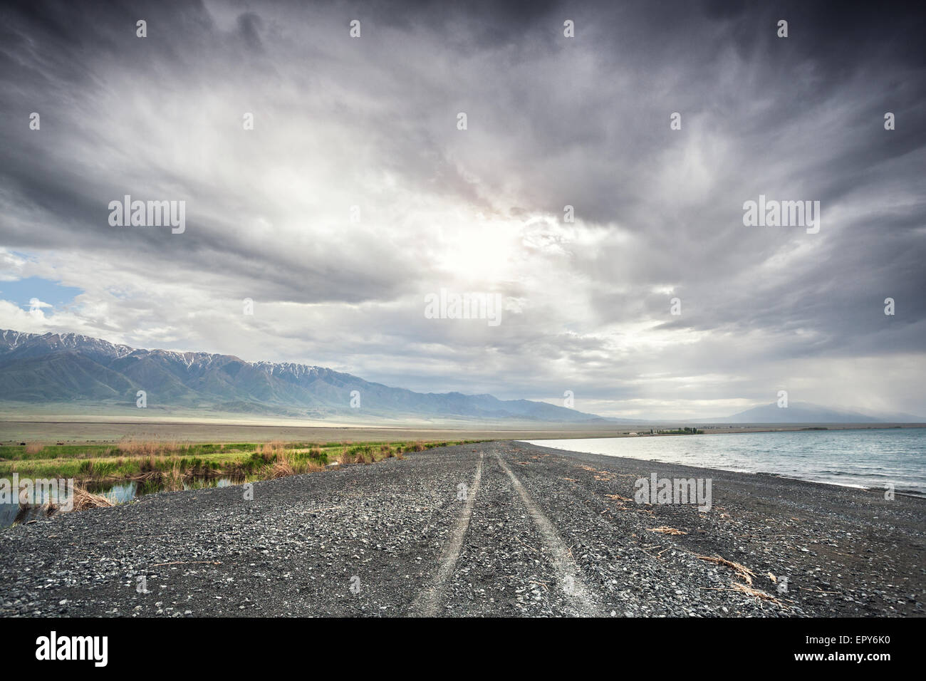 Road near Alakol Lake and mountain scenery at dramatic overcast sky in Kazakhstan, central Asia - Stock Image