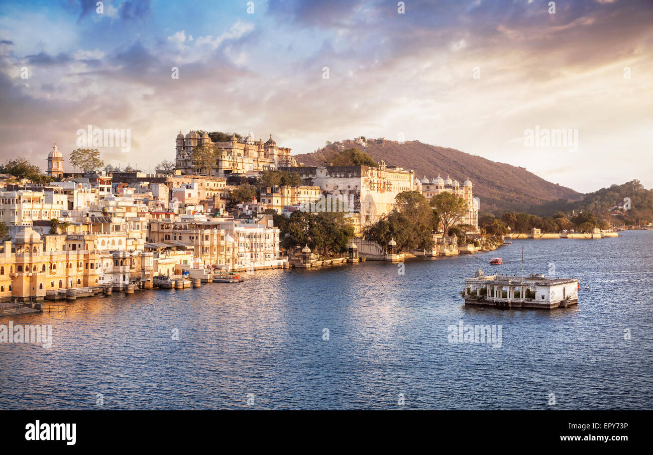 Lake Pichola with City Palace view at cloudy sunset sky in Udaipur, Rajasthan, India - Stock Image
