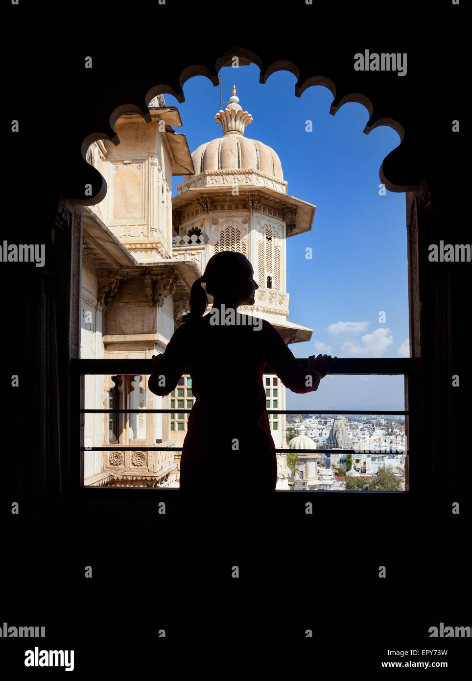 Woman silhouette on the balcony in City Palace museum of Udaipur, Rajasthan, India - Stock Image