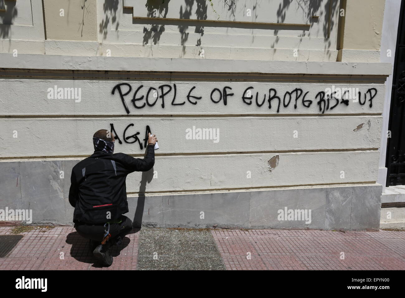 Athens, Greece. 23rd May 2015. A protesters burns paints a graffiti on a wall near the German Embassy that reads - Stock Image