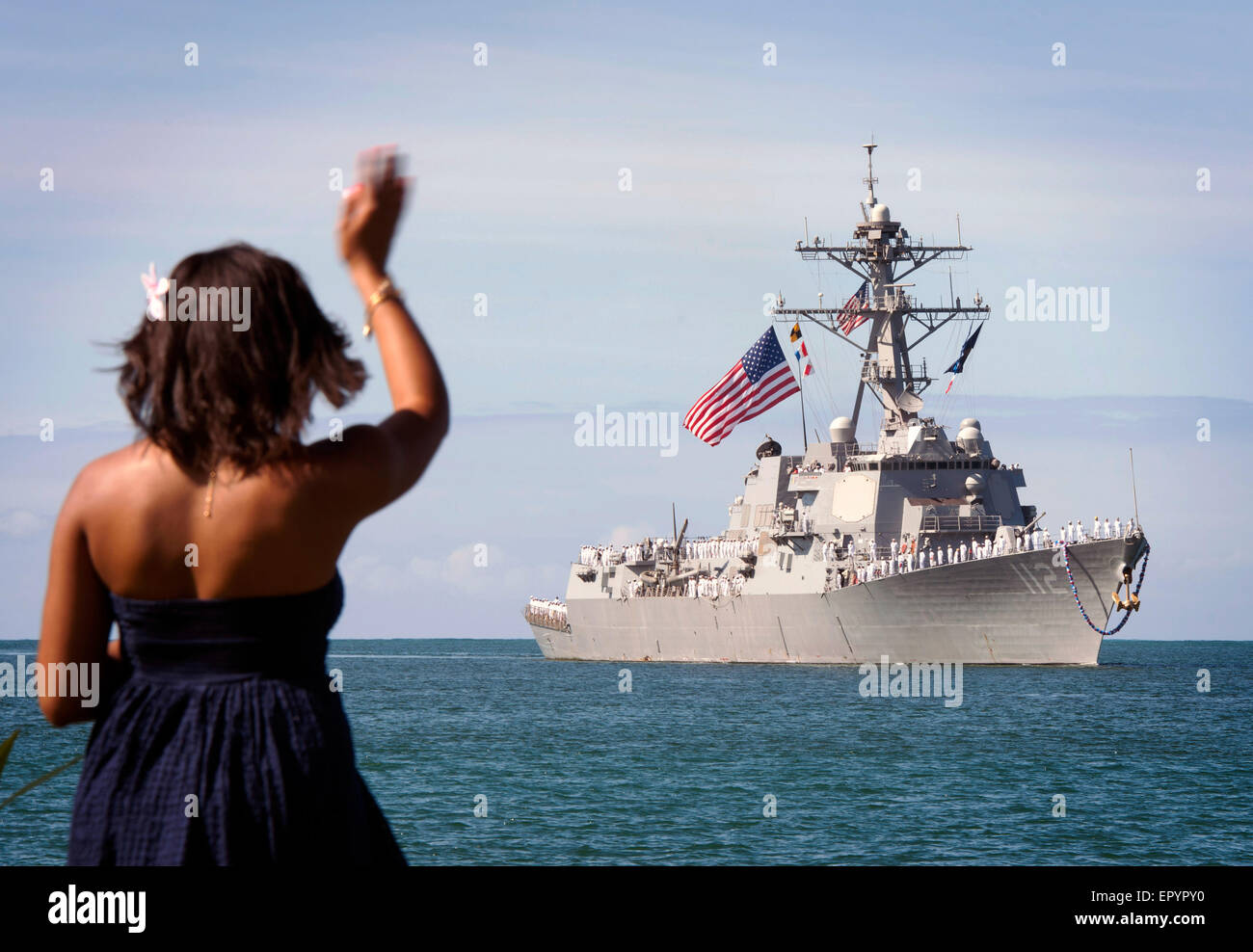 A family member waves to the U.S. Navy guided-missile destroyer USS Michael Murphy as it returns to Joint Base Pearl - Stock Image