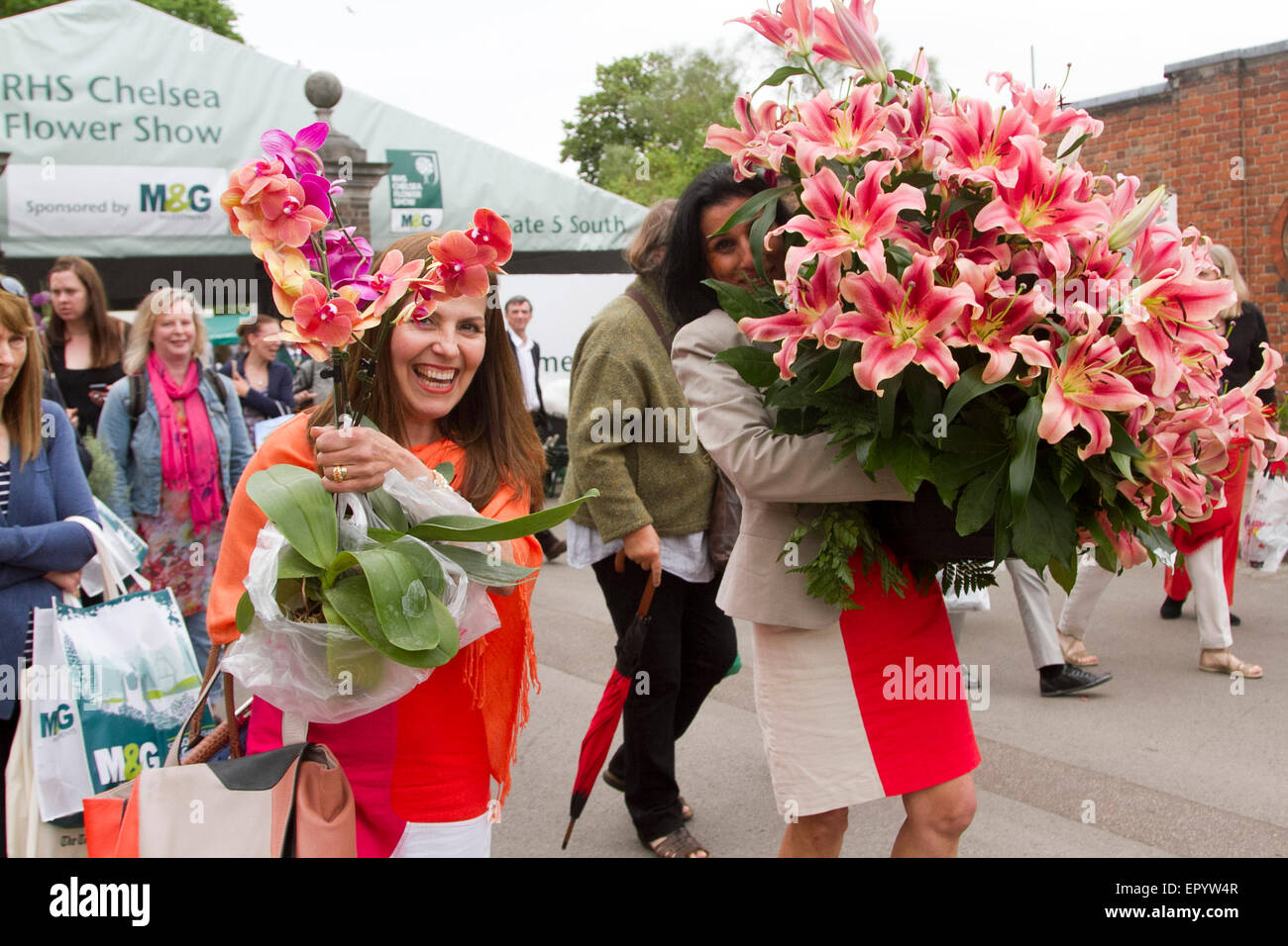 London UK. 23rd May 2015. Members of the public carry colorful  flowers and plants in a sell off on the last day - Stock Image
