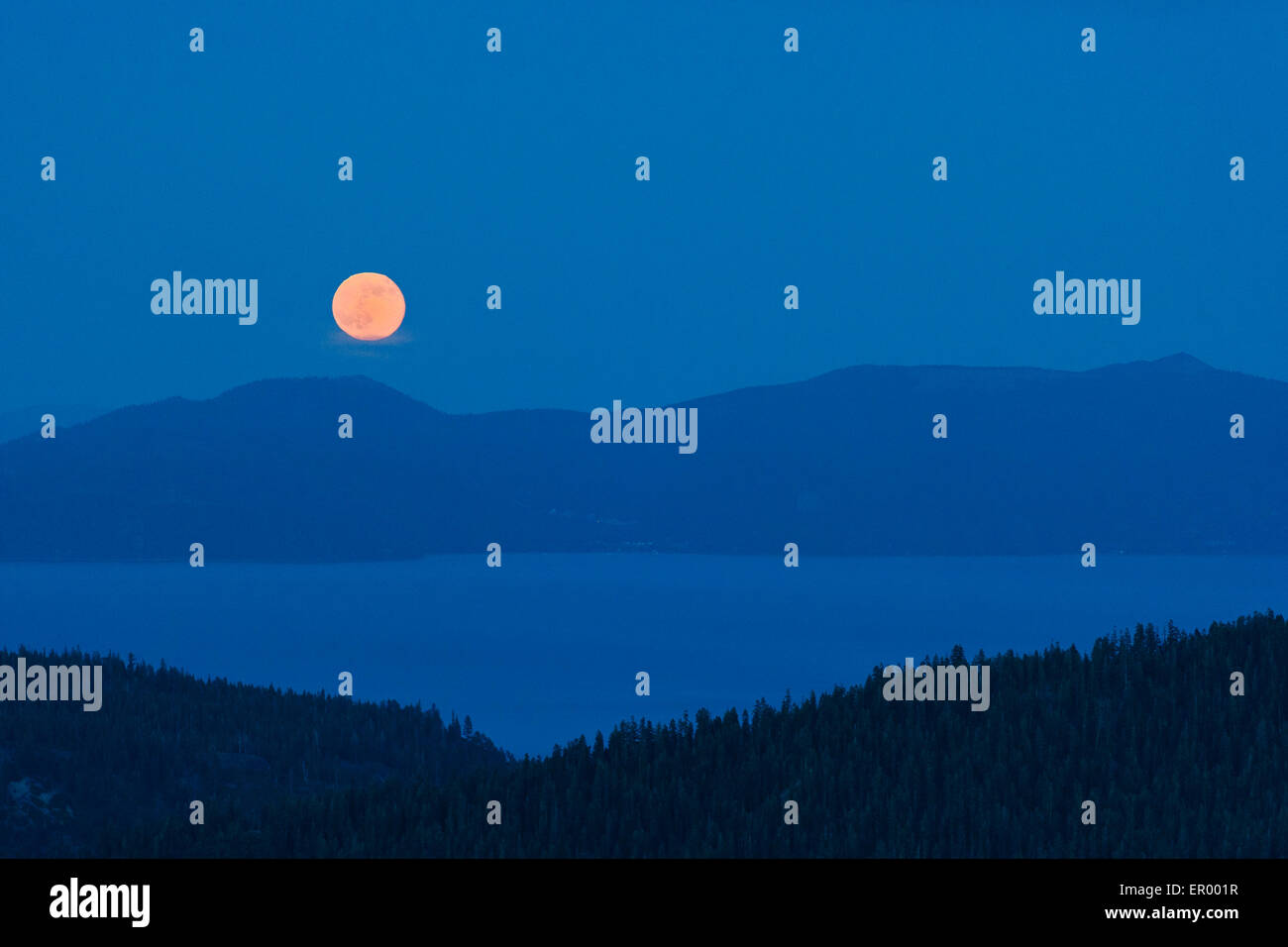 Full moon rising over lake Tahoe as seen from Squaw Valley high camp. - Stock Image