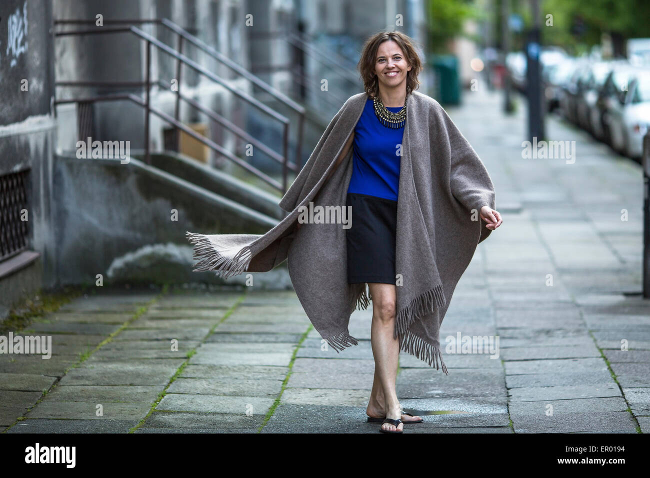 Young positive woman in a poncho walking in the street. - Stock Image