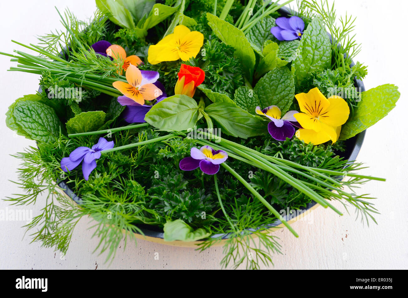 Cooking with herbs concept with fresh herbs and edible flowers in modern yellow fry pan skillet on white wood table. - Stock Image
